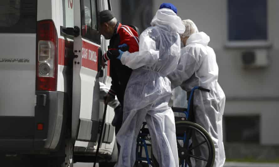 Healthcare workers help a patient into an ambulance in Minsk.