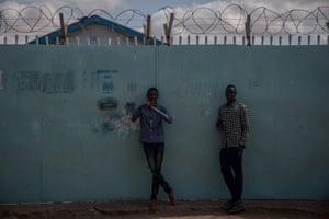 Young men stand in front of a UNHCR field office in Dadaab refugee camp, Kenya