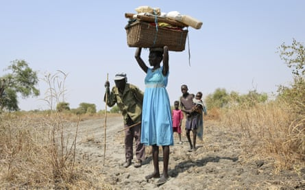 A family displaced by fighting walk into Akobo town, one of the last rebel-held strongholds in South Sudan, after government troops attacked their village.