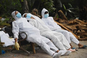 Ambulance staff rest on a bench after their Covid-19 coronavirus duty at a crematorium ground in Guhawati, India