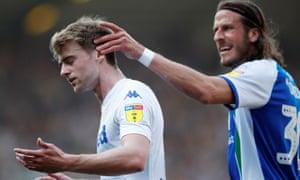 Wigan's Jonas Olsson consoles Leeds's Patrick Bamford