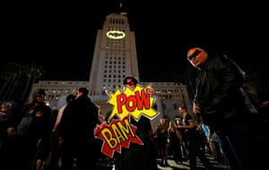 Batman fans Cleeland and de Felicis pose as a bat signal lights up the sky over Los Angeles.