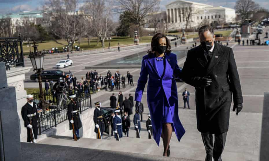 Kamala Harris, in a purple coat and dress by Christopher John Rogers, with her husband, Doug Emhoff, at the inauguration on 20 January.