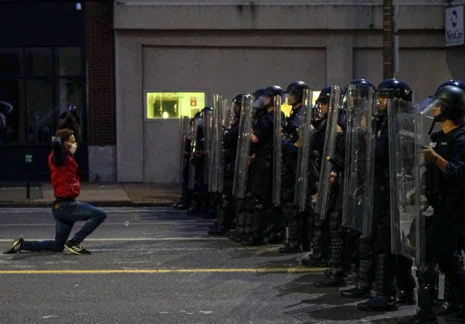 A man gets on his knees in front of police officers during a protest against the death in Minneapolis police custody of African-American man George Floyd, in St Louis, Missouri, U.S. June 1, 2020.