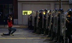 A man gets on his knees in front of police officers during a protest against the death of George Floyd, in St Louis, Missouri.