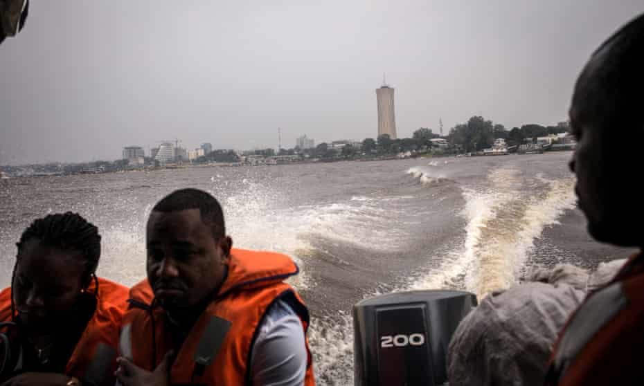 Passengers on the boat between the two capital cities, with Brazzaville's Nabemba Tower in the distance.