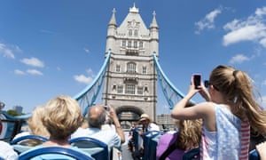 Tourists on an open-top Original London Sightseeing Tour bus