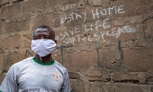 Man poses for a photograph by a wall after the partial lockdown in parts of Ghana to halt the spread of the Covid-19