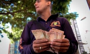 A man counts 100-bolivar bills in a street in Caracas on Tuesday.