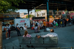 People wait in line for a bus in Corona, Queens.