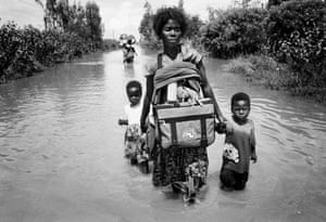 Holding tightly onto her children a mother looks for the safety of higher ground near Chokwe, Mozambique, during the floods which covered the country in 2000