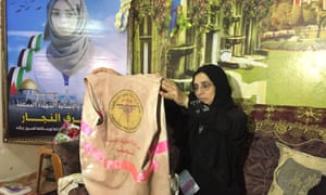 Sabrine al-Najjar holds up the bloodied jacket her daughter, Razan al-Najjar, wore when she was shot by Israeli forces