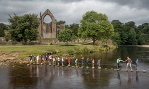 group of kids crossing the river on stepping stones at Bolton Abbey.