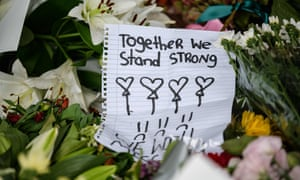A handwritten note  among flowers during a vigil in Christchurch.