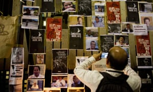 A man takes a picture of images of murdered journalists taped to a fence outside the interior ministry building in Mexico City.
