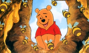 Pooh Bear looks into a beehive.