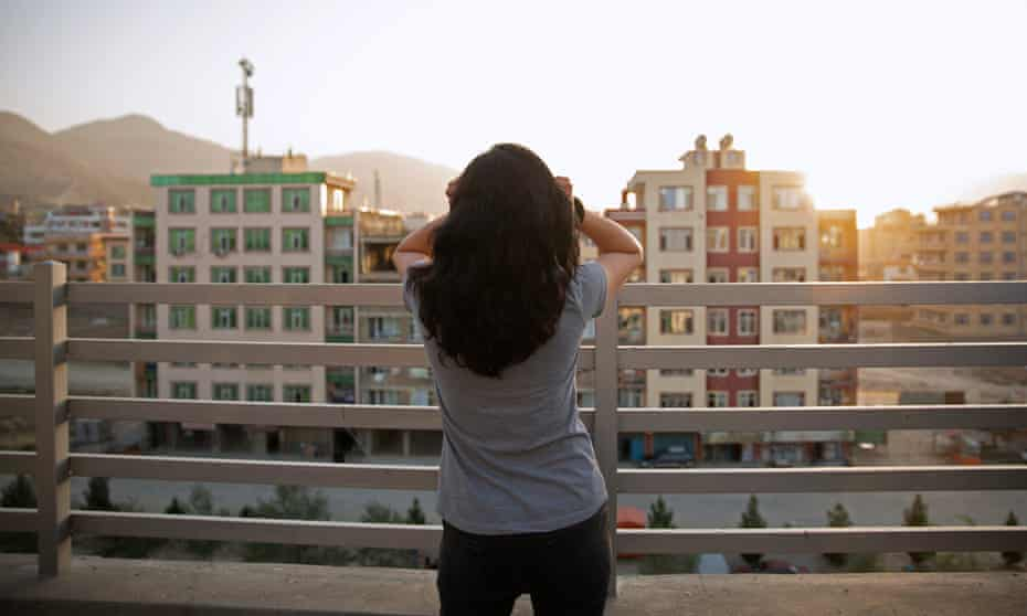 woman looks out at flats from a balcony in Kabul