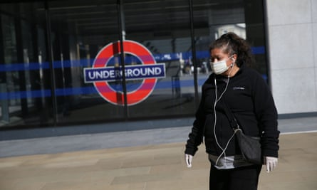 A woman wearing a mask outside King's Cross in London