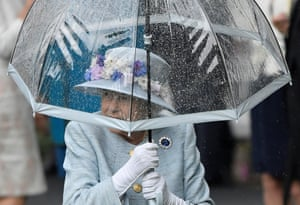 Berkshire, EnglandQueen Elizabeth II shelters under an umbrella during a downpour while attending the races at Royal Ascot.