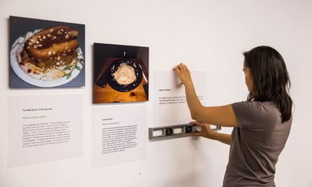 A volunteer with Intersection for the Arts hangs a new gallery of photos