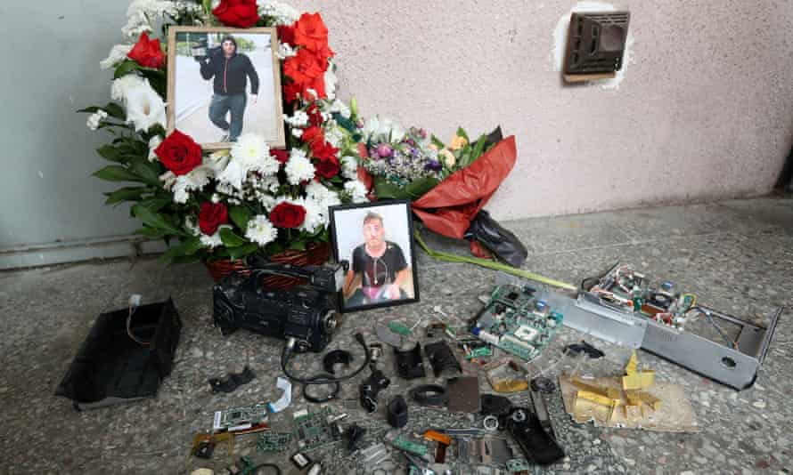 Portraits of journalist Alexander Lashkarava are placed next to a broken camera during his funeral in Tbilisi, Georgia.