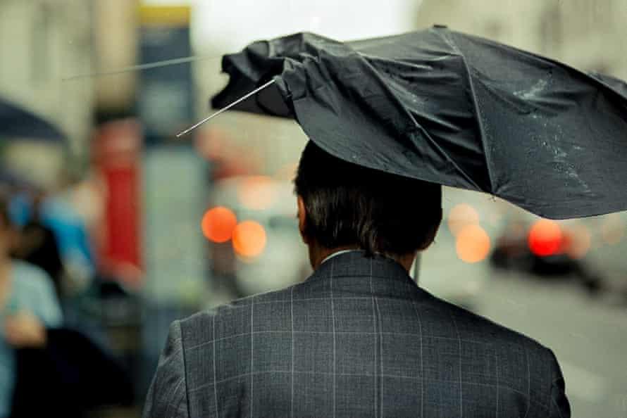 A man with a broken umbrella in Green Park.