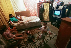 A family watches the Olympic football final on TV while it plays out nearby in the Maracanã stadium