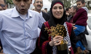 Palestinian teacher Hanan al-Hroub, right, holds her Global Teacher prize at a welcome ceremony upon her return to the West Bank city of Jericho.