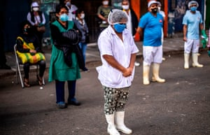 Employees of the Ciudad de Dios market wait to be tested by health ministry workers in Lima, Peru, on 11 May.