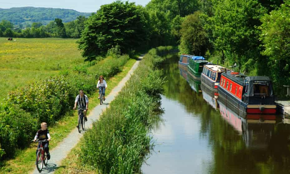 Family cycling past narrowboats on the towpath of the Montgomery Canal
