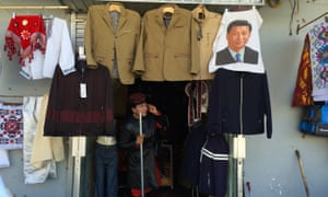 A shopkeeper comes into the street brandishing a metal pole during a regular anti-terror drill in Tashkurga, Xinjiang.