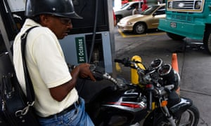 A man pumps fuel into his motorbike at a gas station in Caracas.