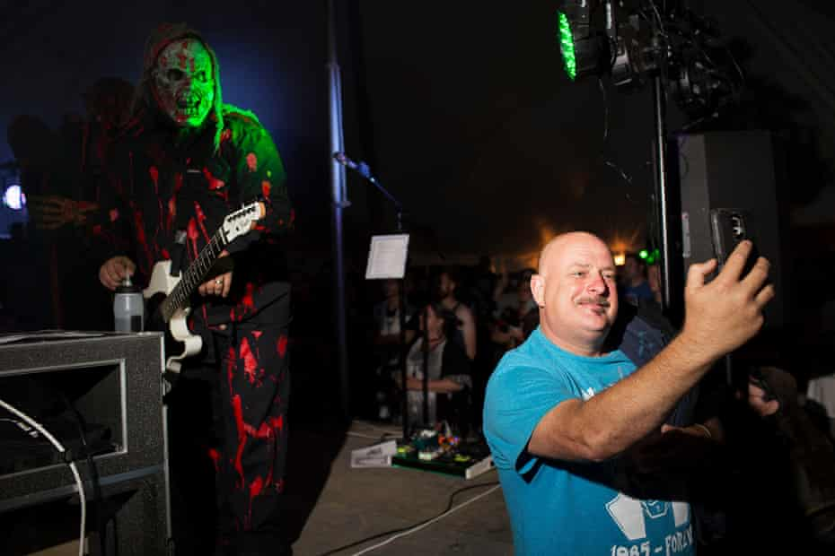 A fan takes a selfie with Christian metal band Grave Robber.