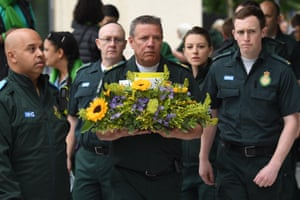 London ambulance service staff bring flowers in memory of the dead
