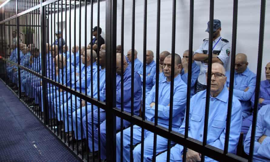 Muammar Gaddafi-era officials wait for their trial in a prison cage in Tripoli.