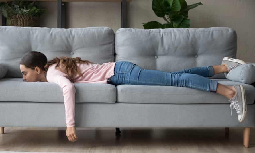 A bored woman lies face down on her sofa.