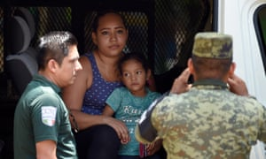 Mexican migration officers and members of the national guard detain a Nicaraguan migrant with her daughter on the banks of the Suchiate river in Ciudad Hidalgo, Chiapas state, Mexico on Saturday.
