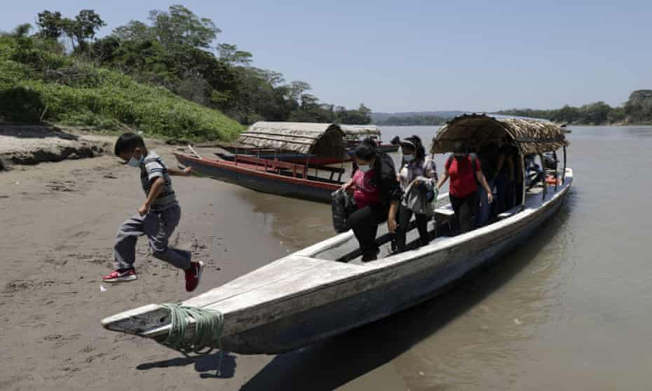 Migrants trying to reach the US disembark in Frontera Corozal, Mexico, after crossing the Usumacinta River from Guatemala