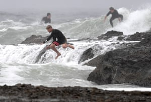A surfer jumps into the surf at Snapper Rocks