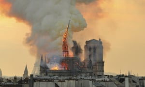 The flaming spire of Notre Dame Cathedral topples into the roof.