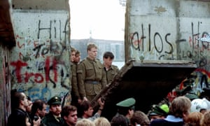 East German border guards look through a hole in the Berlin Wall in November 1989