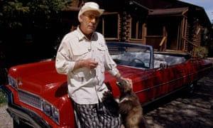 Fear and petting … Thompson with his pet wolverine and his cherry-red Pontiac at his Colorado cabin.