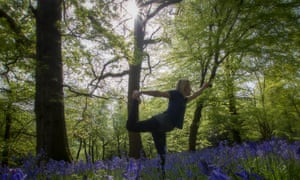 woman doing a yoga pose in bluebell woodland