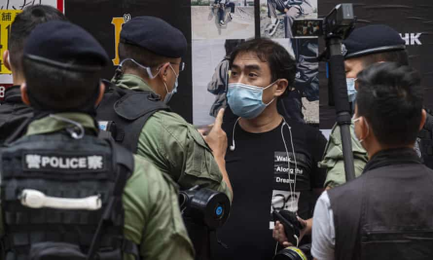 Riot police officers stop and search a protester during a protest in Hong Kong at the beginning of October.