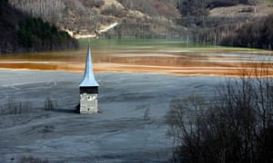 The church spire of Geamana village is submerged by toxic water tainted with cyanide and other chemicals from a copper mine begun in the 1970s near Roșia Montană.