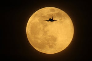 A plane flies in the sky in front of the largest Supermoon of 2019 in London.
