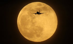 A plane flies in front of the supermoon in London on 19 February, 2019.