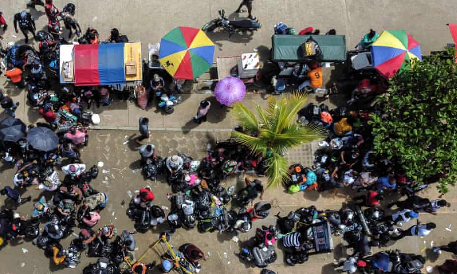 An aerial view of stranded migrants from Cuba, Haiti, Venezuela and several African countries at the entrance of a port as they board a boat to leave Necoclí.