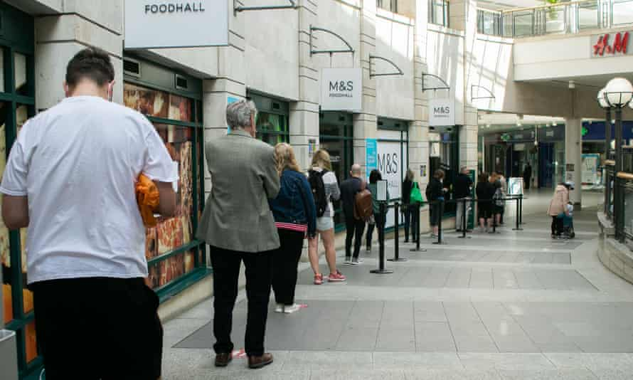 Shoppers in Wimbledon, south London, wait in line 2 metres apart, following government advice.