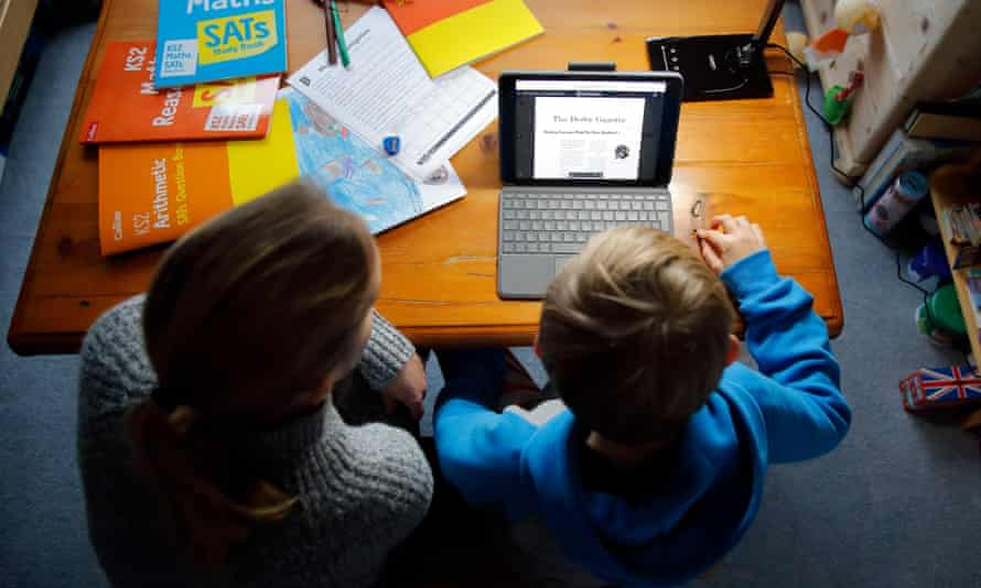 Top-down view of mother sat at table, helping son with school work